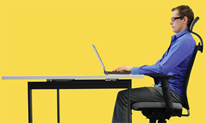 a yellow background banner of a white male sitting in an ergonomic chair at a desktop and working with a laptop